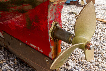 propel: Propeller of a fishing boat, grounded on a pebble beach