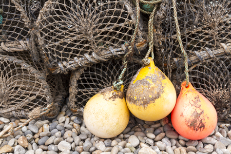 lobster pots: Stacked lobster pots, with buoys on an English pebbled beach  Stock Photo