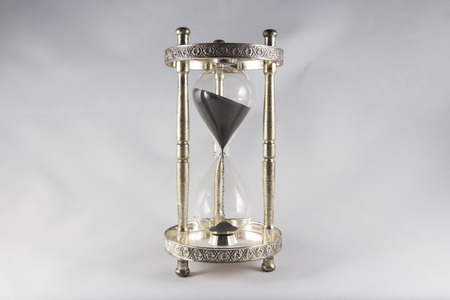 centred: Antique hourglass, black sand, textured background. Centre image, landscape, top half mostly full.