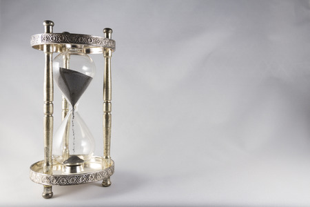 centred: Antique hourglass, black sand, textured background. Left of image, blank space on right , landscape, top half almost full.