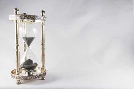 mortality: Antique hourglass, black sand, textured background. Left of image, blank space on right , landscape, top half running out.