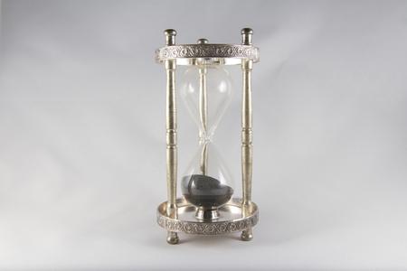 mortality: Antique hourglass, black sand, textured background. Centre image, landscape, top half empty.