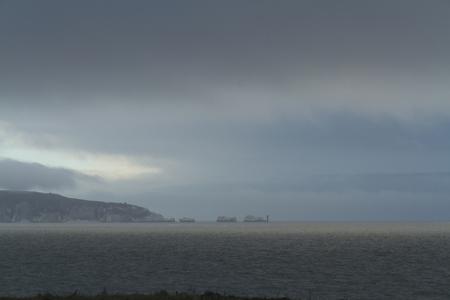 long shot: Tiro lungo di aghi e Faro, Isola di Wight, Inghilterra, Regno Unito Stormy cielo
