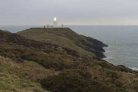 pembrokeshire: Light house on Strumble Head, Ynysmeicl or St. Michael%u2019s Island Near Fishguard, Pembrokeshire, Wales Stock Photo