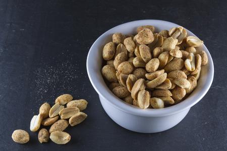 monosodium glutamate: Bowl of dry roast peanuts on slate mat