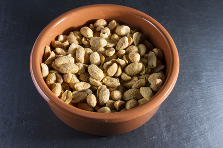 glutamate: Bowl of dry roast peanuts on slate mat.