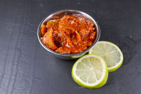 accompaniment: Indian chutney lime pickle in metal bowl. Accompaniment for poppadoms and Two lime slices. Stock Photo