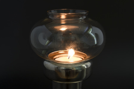 glass topped: Candle flame in glass topped antique lamp, in darkened area.
