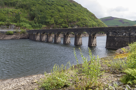 elan: Arches of Submerged Dam, with road on top. Garreg-ddu Reservoir, Elan Valley, Powys, Wales, United Kingdom, Europe. Stock Photo