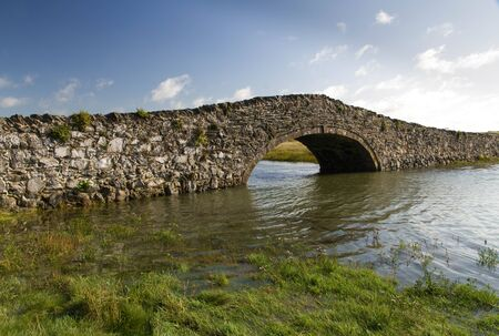 eighteenth: Eighteenth Century stone hump back bridge, with water channel and blue sky. Aberffraw, Anglesey, Wales, United Kingdom, Europe Stock Photo