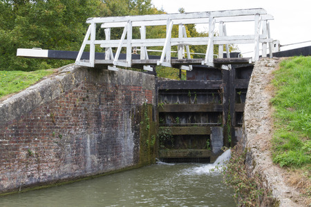 canal lock: Water spraying through gates of canal lock. Bottom gates of full lock. Kennett and Avon Canal, Devizes, Wiltshire, England, United Kingdom, Europe