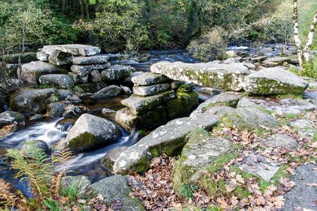 granite park: Partially collapsed ancient stone clapper bridge. Dartmeet, Dartmoor National Park, Devon, England, United Kingdom. Granite Bridge, autumn, fall, long exposure.