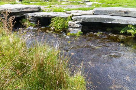 empedrado: El agua que fluye por debajo de puente de piedra pavimentada.