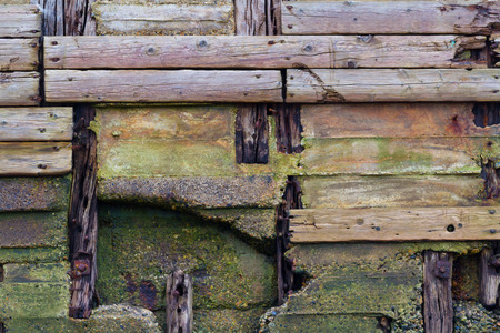 decaying: Detail of old pier, wooden planks weathered, crossing and decaying.