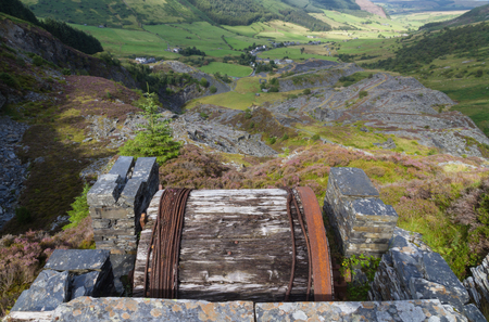 to incline: Looking down the welsh valley of Cwm Penmachno derelict incline drum house  disused slate quarry in foreground. Snowdonia Wales United Kingdom Stock Photo
