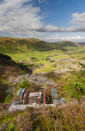 incline: Looking down the welsh valley of Cwm Penmachno derelict incline drum house  disused slate quarry in foreground. Snowdonia Wales United Kingdom Stock Photo