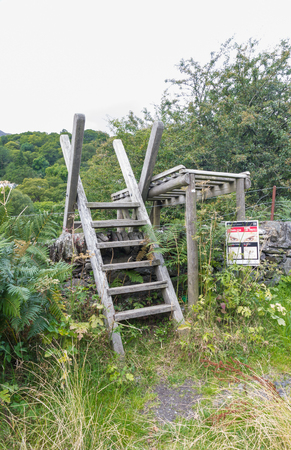 stile: Typical ladder stile over dry stone wall Snowdonia National Park Gwynedd Wales United kingdom. Stock Photo