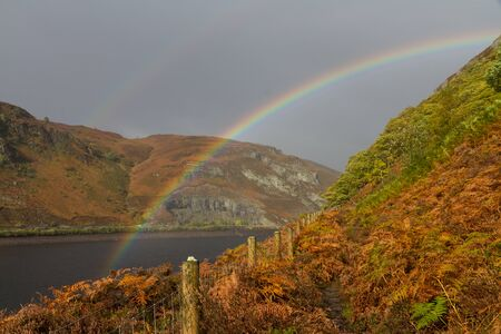 elan: Rainbow over the The Garregddu Reservoir in mid Wales surrounded by hills. In Autumn or Fall. Elan Valley Powys Wales United Kingdom Europe. Stock Photo