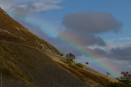 a slope: Rainbow with mountain slope.