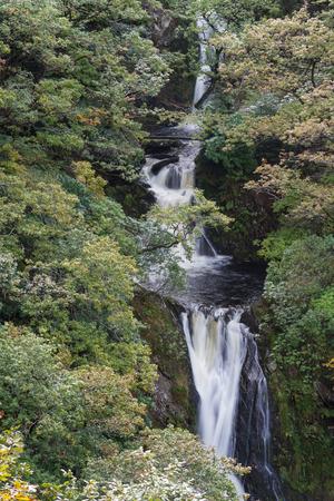 Mynach Falls or Rhaeadr Mynach a waterfall in Autumn or Fall. Devils Bridge, Pontarfynach, Hafod estate, Ceredigion, Wales, United Kingdom, Europe. Фото со стока