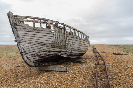 dungeness: Old wooden boat, with rails for moving boats. Dungeness Beach, Kent, England, United Kingdom. Stock Photo