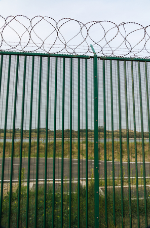 deter: Boundary area of ferry terminal. Fence and Razor wire to deter refugees, asylum seekers. Dunkirk, France, Europe. Ferries to the UK. Migrants are trying to get to the United Kingdom from French ports