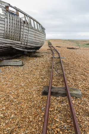 dungeness: Part of old wooden boat, with rails for moving boats. Dungeness Beach, Kent, England, United Kingdom.