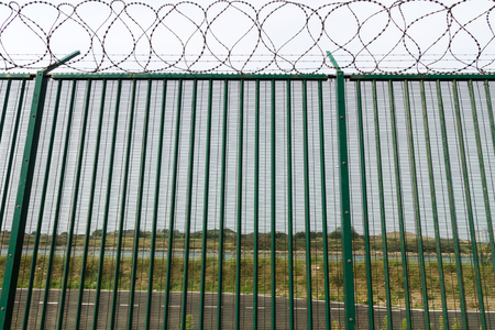 razor wire: Boundary area of ferry terminal. Fence and Razor wire to deter refugees, asylum seekers. Dunkirk, France, Europe. Ferries to the UK. Migrants are trying to get to the United Kingdom from French ports
