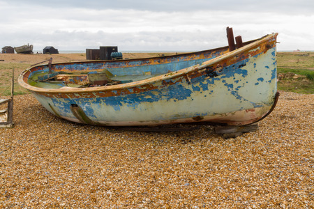 dungeness: Old wooden boat with flaking paint. Dungeness Beach, Kent, England, United Kingdom.