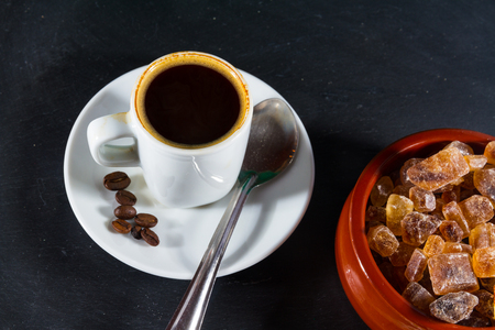 expresso: German Rock Sugar, brauner Kandis in a terracotta brown bowl with cup of expresso coffee.