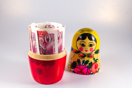 matreshka: Roll of 50 pound sterling notes hidden in matryoshka Russian doll. Stock Photo