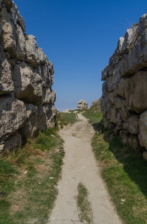 dorset: Path in disused limestone quarry, between two huge limestone block walls. Fortuneswell, Weymouth, Dorset, England United Kingdom. Stock Photo