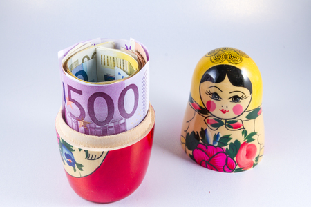 hidden taxes: Roll of 50 Euro notes hidden in matryoshka Russian doll.