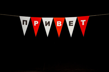 cyrillic: Privet in Cyrillic Russian on red and white bunting for hello welcome page. Black background.