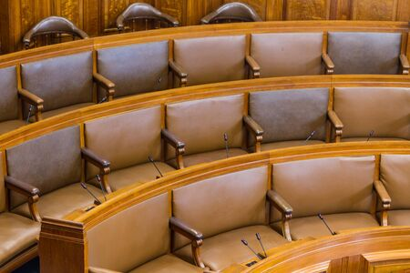 upholstered: Wood and leather seats in a council chamber. Wood and leather upholstered.