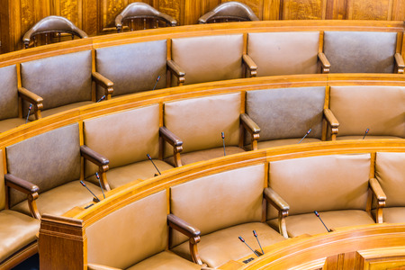 bureaucratic: Wood and leather seats in a council chamber. Wood and leather upholstered.