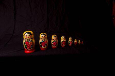 muñecas rusas: Conjunto de muñecas rusas Matryoshka en fila, sobre fondo negro.