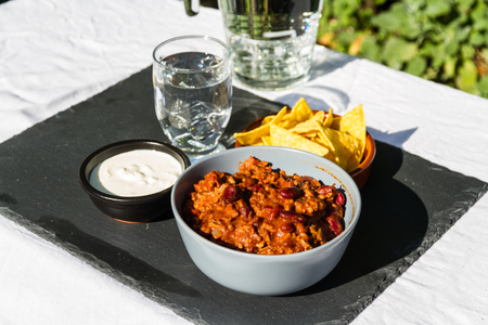 Home made Chilli Con Carne in orange ceramic bowl and tortilla chips and soured cream on the side with jug and glass of iced water. On slate mat, outside on linen covered table. Evening light
