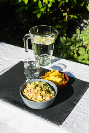 Home made guacamole in ceramic bowl and tortilla chips and soured cream on the side with jug and glass of iced water. On slate mat, outside on linen covered table. Evening light. Stock Photo