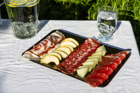 al fresco: Italian antipasto meat platter outside in evening light.  Salami, ham, pancetta, pear and melon. Served with iced water.