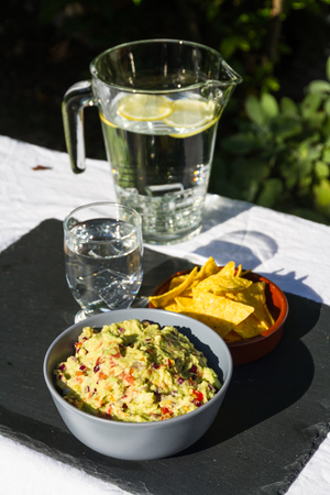 soured: Home made guacamole in ceramic bowl and tortilla chips and soured cream on the side with jug and glass of iced water. On slate mat, outside on linen covered table. Evening light. Stock Photo