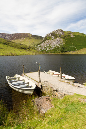 Two boats moored to Jetty by small lake. Llyn y Dywarchen Reservoir, Rhyd Ddu, Gwynedd, Wales, United Kingdom