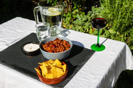 soured: Home made Chilli Con Carne in orange ceramic bowl and tortilla chips and soured cream on the side with jug and glass of iced water. On slate mat, outside on linen covered table. Stock Photo