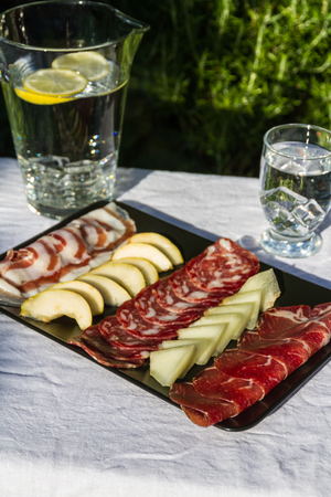 italian fresco: Italian antipasto meat platter outside in evening light.  Salami, ham, pancetta, pear and melon. Served with iced water.