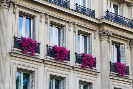 Vieille grande façade avec des fleurs rouges dans les boîtes de fenêtre. Paris, France, Europe.