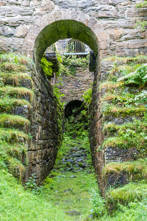 nant: Pit that once housed the water wheel in the ruin of the Pont y Pandy slate processing mill. Snowdonia, North Wales, United Kingdom Stock Photo