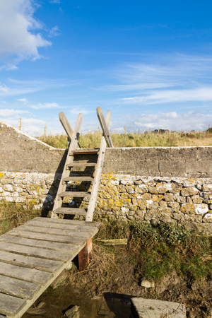 Typical ladder stile, over wall, with bridge over ditch. Aberthaw beach, South Wales, United Kingdom, Europe.