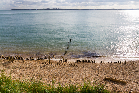 Pebble beach with worn defences and Isle of Wight in distance. Lepe Country Park, Exbury Southampton, Hampshire, England, United Kingdom