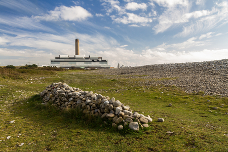generating station: Pile of stones with Aberthaw B Coal Fired Power Station, South Wales, UK.