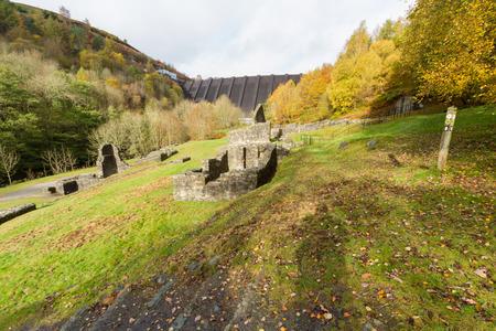 footbridges: Ruins of Bryntail Lead Mine, the Clywedog Dam in the distance. Llanidloes, Powys, Wales, United Kingdom.